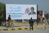 Iraqis walk by a poster announcing the upcoming visit of Pope Francis and a meeting with revered Shia Muslim leader, Grand Ayatollah Ali al-Sistani, right, in Najaf, Iraq [Anmar Khalil/AP]