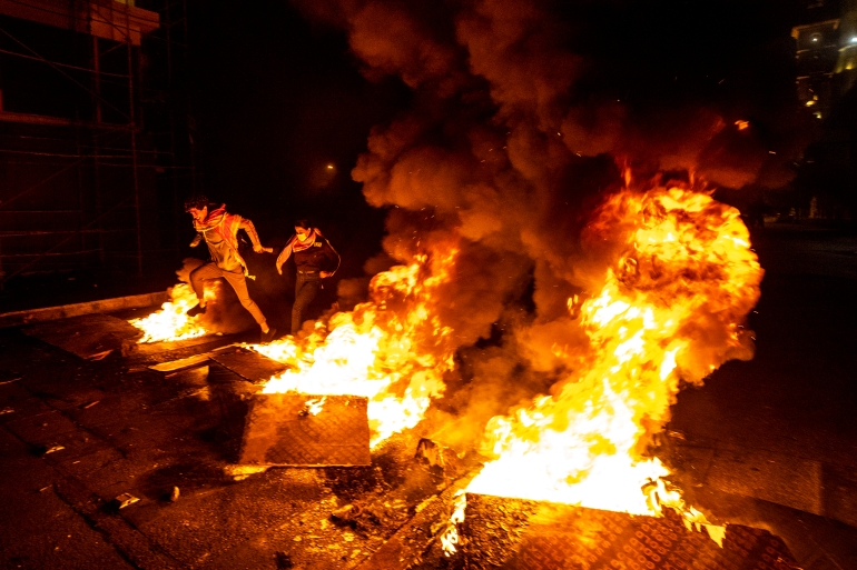 Protesters jump over burning tires that were set on fire to block a road, at Martyrs Square, in downtown Beirut, Lebanon, Saturday, March 6, 2021 [Hassan Ammar/ AP]