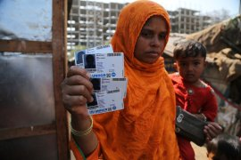 Rahima Kato, a Rohingya woman, displays identity cards of her family members issued by the United Nations High Commissioner for Refugees (UNHCR) at their makeshift camp on the outskirts of Jammu [File: Channi Anand/AP]