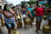 Women wearing masks amid the COVID-19 pandemic wait to buy cooking gas from the Petrobrás Oil Tankers Union, part of a solidarity campaign to sell fuel at low prices in the Vila Vintem favela of Rio de Janeiro on March 12, 2021 [AP/Bruna Prado]