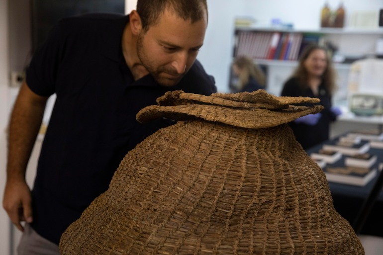 Archeologist Haim Cohen looks at a 10,500-year-old woven basket found during a sweep of caves in the desert [Sebastian Scheiner/AP]