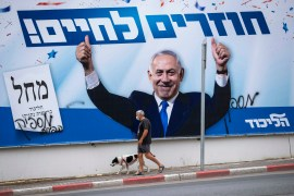 A man walks his dog by an election campaign billboard for the Likud party that shows its leader Prime Minister Benjamin Netanyahu under the slogan 'Back to life' in Ramat Gan, Israel on March 22, 2021 [AP/Oded Balilty]