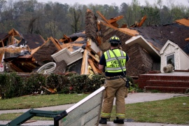 A firefighter surveys damage to a house south of Birmingham, Alabama [Butch Dill/AP]
