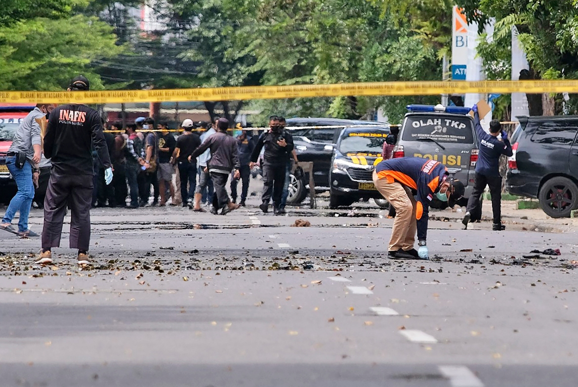 Police officers inspect the area near the church where the explosion took place. [Masyudi S Firmansyah/AP Photo]