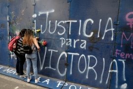 Women putting flowers on the perimeter wall of the Quintana Roo state offices sprayed with graffiti that reads 'Justice for Victoria', during a protest in Mexico City [Eduardo Verdugo/AP Photo]