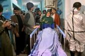Afghans carry the body of one of the three women journalists killed in Jalalabad city [Sadaqat Ghorzang/AP]