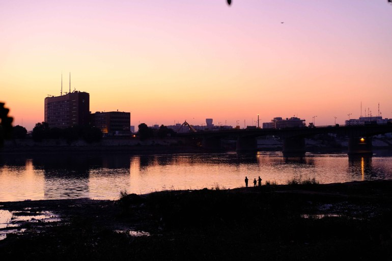 People on the bank of the Tigris river at sunset in Baghdad, Iraq on December 6, 2020 [Nabil Salih/Al Jazeera]