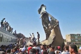 A screengrab shows people gathered around the wreckage after two trains collided in Tahta district of Sohag province on Friday [AFP]