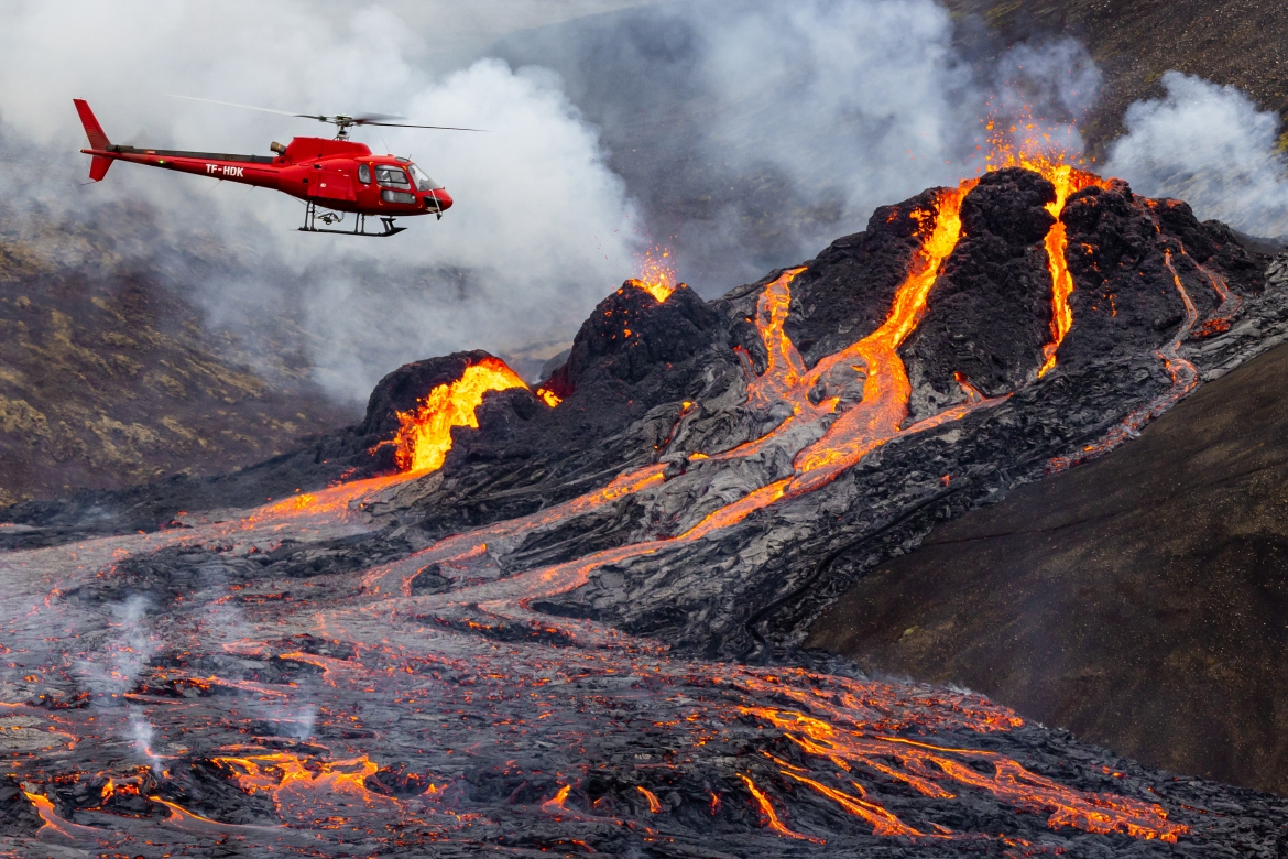 A helicopter flies close to a volcanic eruption which began in Fagradalsfjall near the capital, Reykjavik. [Vilhelm Gunnarsson/Getty Images]