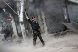 Ali, a rebel fighter, gestures for victory after firing a shoulder-fired rocket towards a building where Syrian troops loyal to President Bashar al-Assad were hiding as they attempted to gain terrain against the rebels during heavy clashes in the Jedida district of Aleppo, Syria, on November 4, 2012 [Narciso Contreras]