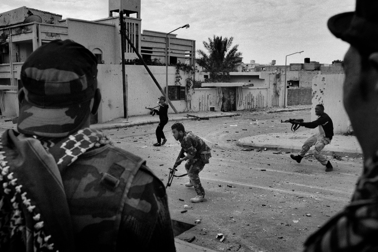 Anti-Gaddafi fighters from Benghazi engage in a firefight with snipers who are loyalists to Colonel Muammar Gaddafi during a street fight in Gaddafi's hometown of Sirte, Libya, on October 19, 2011 [Mauricio Lima]