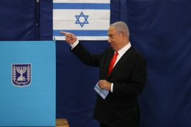 Israeli Prime Minister Benjamin Netanyahu prepares to cast his ballot at a polling station in Jerusalem on Tuesday [Ronen Zvulun via AP]