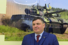 Yuri Husyev, head of Ukroboronprom, stands next to a photo of the Oplot battle tank [Mansur Mirovalev/Al Jazeera]
