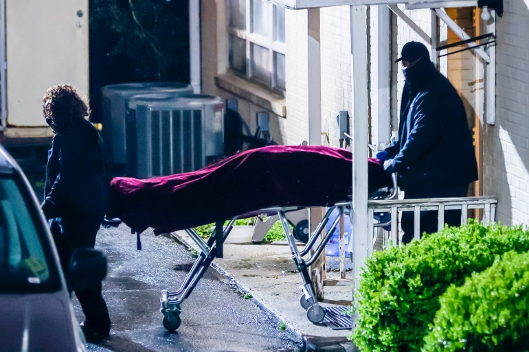 Officials with the Fulton County Medical Examiner's office remove a body from the Gold Spa massage parlor after a shooting on Piedmont Road in Atlanta [Erik S. Lesser/EPA]