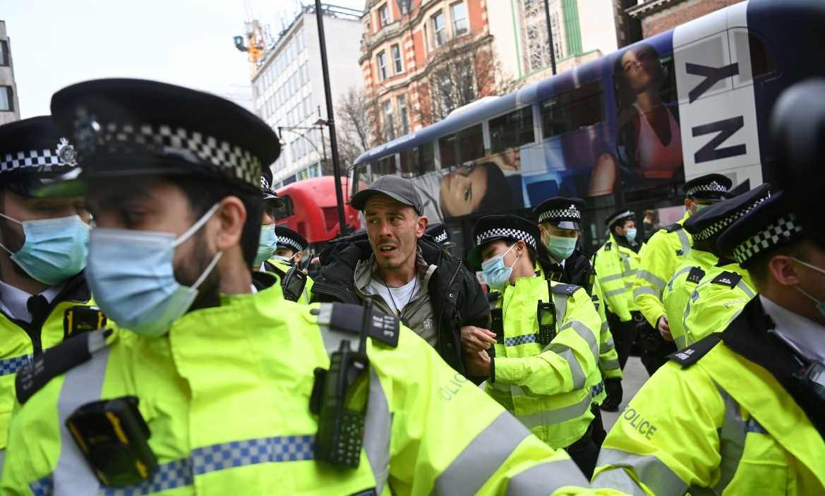 Police detain a protester during an anti-lockdown demonstration in London, UK. [Neil Hall/EPA]