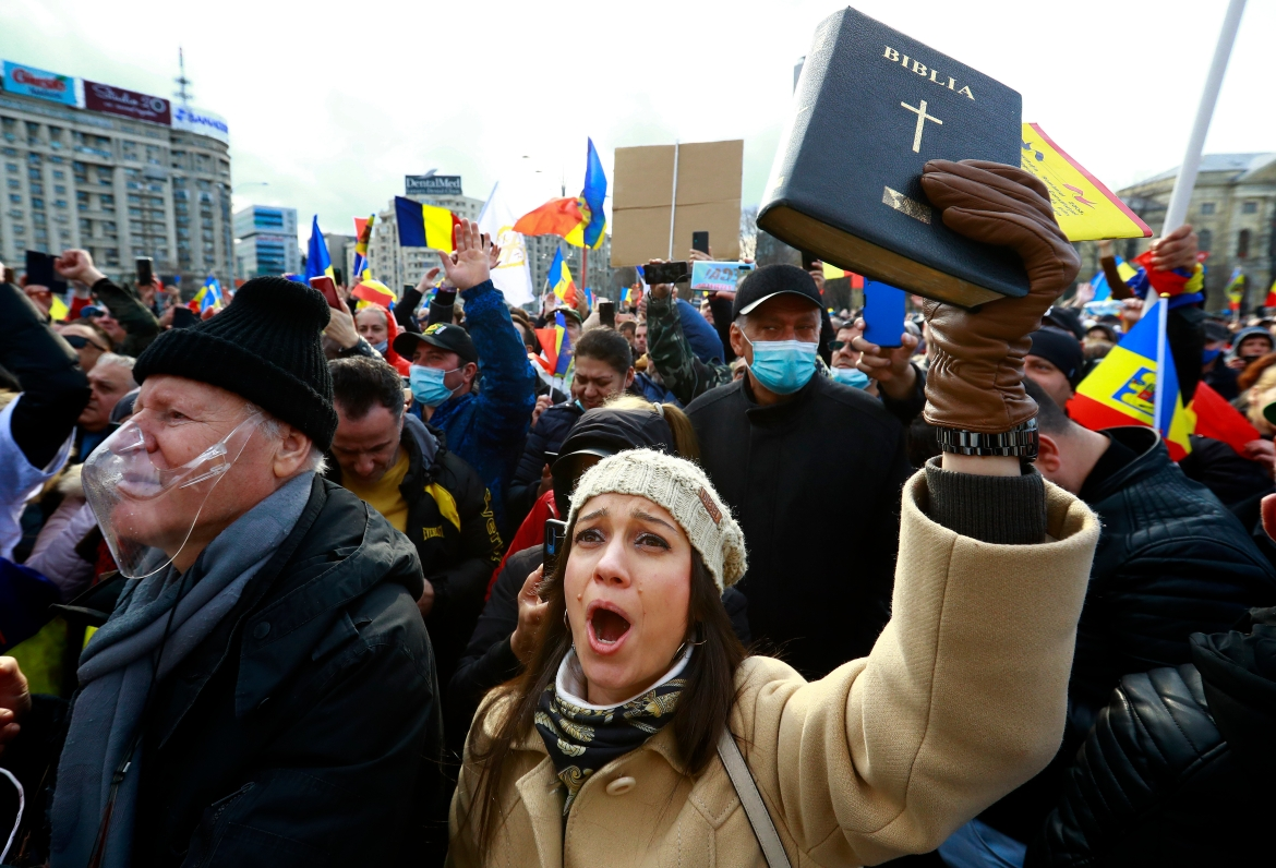 A woman waves a bible while shouting anti-government slogans during a protest in front of government headquarters in Bucharest, Romania, against a new mandatory vaccination law project and against new measures ordered by the government during the third wave of the COVID pandemic [Robert Ghement/EPA]