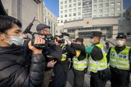 Police attempt to stop journalists from recording footage outside a court in Shanghai during the trial of Chinese citizen journalist Zhang Zhan [File: Leo Ramirez/AFP]