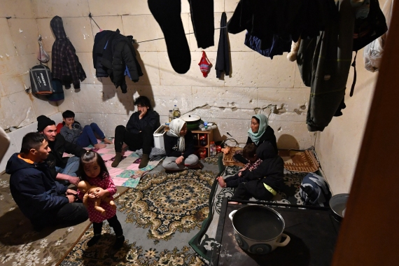 Members of three different Afghan families shelter from sub-zero temperature outside in an abandoned house near the Bosnia - Croatia border, in the northern Bosnian village of Bosanska Bojna, [File: Elvis Barukcic/AFP]