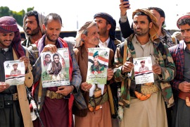Fighters loyal to the Houthis hold up posters with the portraits of fallen comrades killed in recent battles, during a mass funeral for them at al-Saleh Mosque in Yemen's capital Sanaa on February 16, 2021 [File: AFP/ Mohammed Huwais]