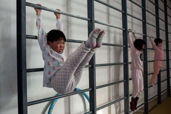 Young gymnasts train at the Li Xiaoshuang Gymnastics School. They are among the latest recruits to China's notoriously demanding state sports system. [Nicolas Asfouri/AFP]