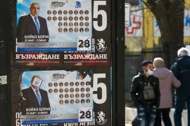 People walk past election posters of Bulgarian Prime Minister and leader of centre-right GERB party Boyko Borissov in Bankya ahead of the general election[Nikolay Doychinov/AFP]