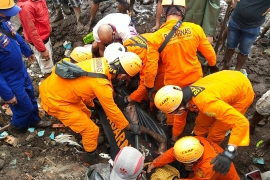 This handout photo taken on April 5, 2021 and released by the National Search and Rescue Agency (BASARNAS) shows rescuers retrieving a victim's body in Nelemamadike village, East Flores, after torrential rains triggered floods and landslides in Indonesia and East Timor [Handout/ BASARNAS via AFP]