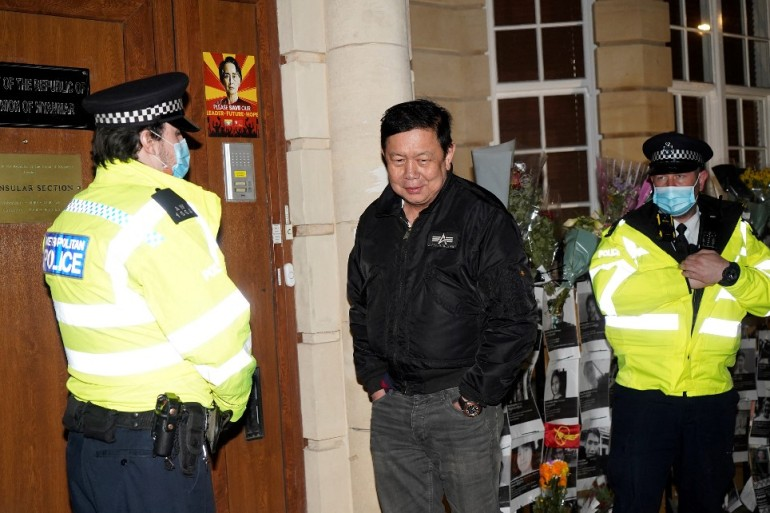 Myanmar's Ambassador to the United Kingdom, Kyaw Zwar Minn, stands with police officers locked outside the Myanmar Embassy in London on Wednesday evening [Niklas Halle'n/AFP]