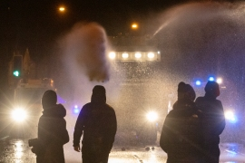 Police officers use water cannon as they clash with nationalist youths in the Springfield Road area of Belfast as disorder continued following days of mainly loyalist violence [Paul Faith/AFP]