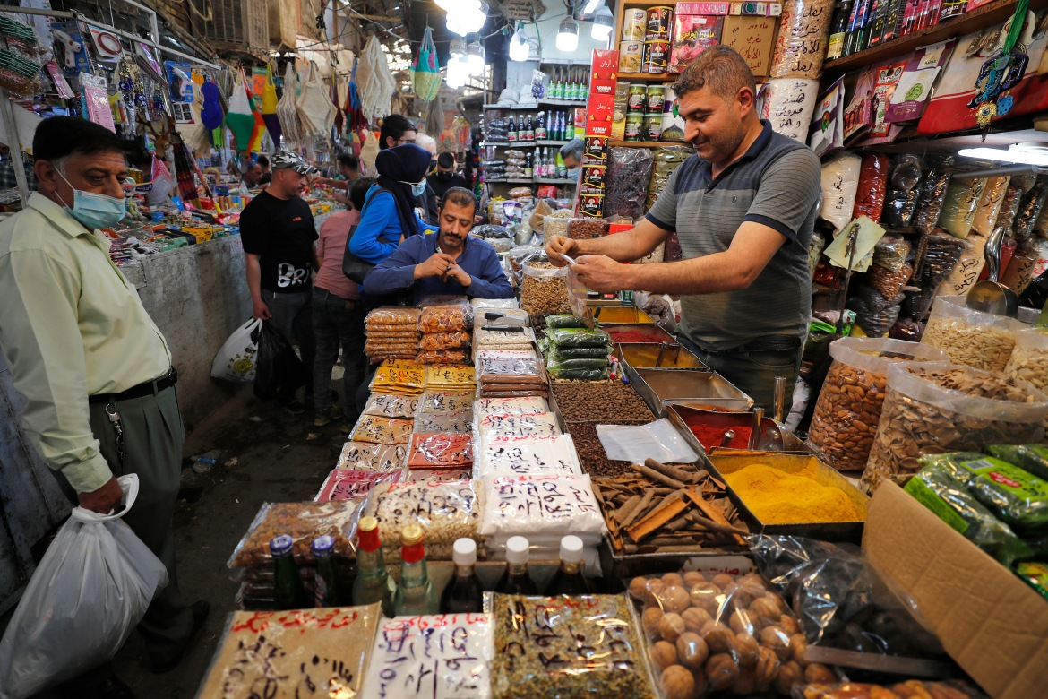 An Iraqi man sells food at the Shorjah market in central Baghdad ahead of the Muslim holy month of Ramadan after the easing of the curfew imposed by authorities amid the COVID-19 pandemic. [Ahmad Al-Rubaye/AFP]