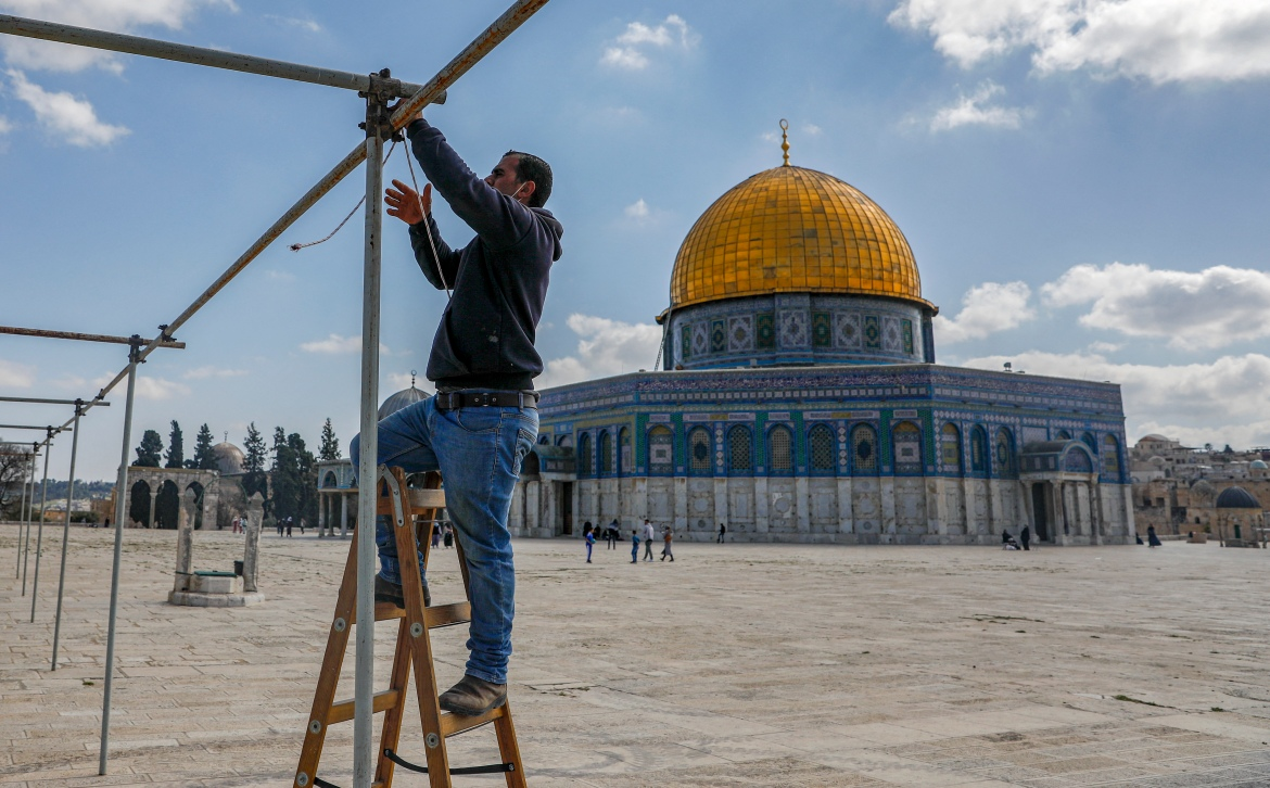 A Palestinian man erects scaffolding to be used to shade worshippers with canvases during the day, near the Dome of the Rock at the Al-Aqsa Mosque compound, Islam's third-holiest site, in the old city of Jerusalem, on the eve of the Muslim holy fasting month of Ramadan. [Ahmad Gharabli/AFP]
