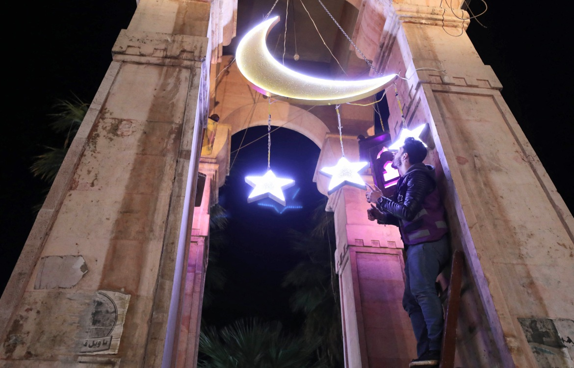 A Syrian man adjusts decorations for the Muslim holy month of Ramadan at the Clock Square in Syria's rebel-held northwestern city of Idlib.  [Omar Haj Kadour/AFP]