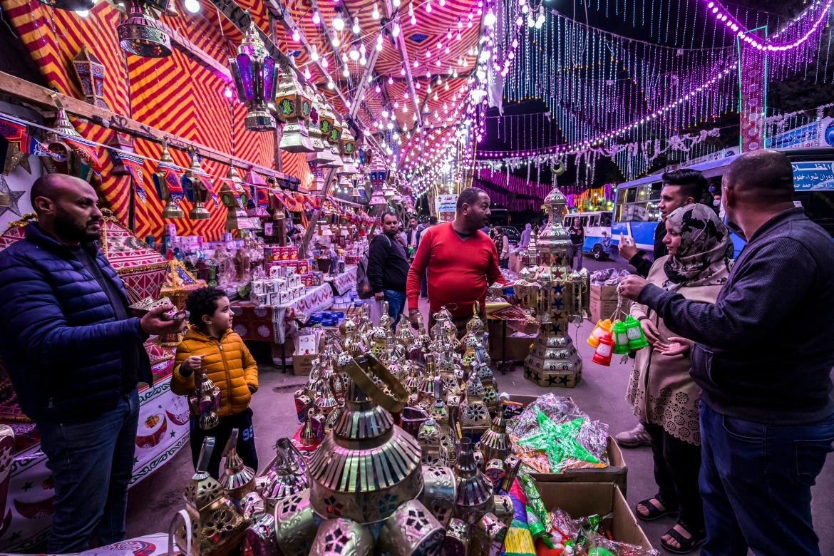 People shop from a stall selling Ramadan lanterns along a main street in the northern suburb of Shubra of Egypt's capital Cairo at the start of the Ramadan. [Khaled Desouki/AFP]