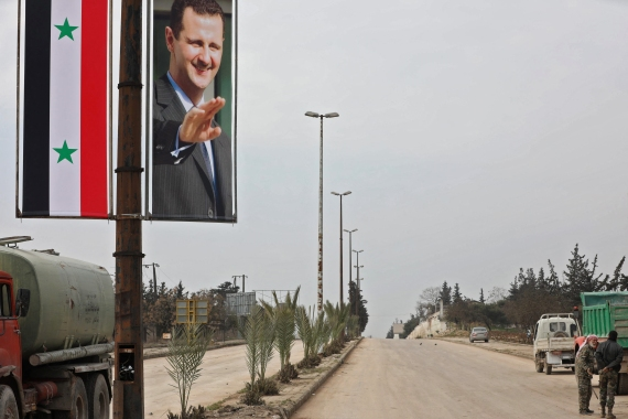 A photo taken on February 18, 2020 during a guided tour organised by the Syrian Ministry of Information shows a poster of Syrian President Bashar al-Assad adorning the M5 highway connecting Aleppo to Damascus. [Louai Beshara/ AFP]