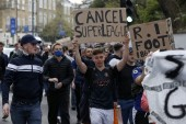 Football supporters demonstrate against the proposed European Super League outside of Stamford Bridge football stadium in London on Tuesday [Adrian Dennis/AFP]