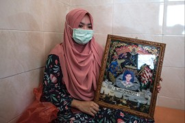Berda Asmara shows a photo of her sailor husband Mes Guntur Ari Prasetyo at their home in Surabaya as the search continued for the missing Indonesian navy submarine with 53 crew on board [Juni Kriswanto/AFP]