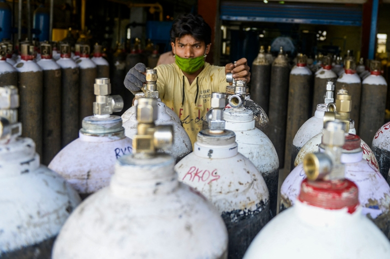 A worker arranges medical oxygen cylinders to transport to hospitals for the coronavirus treatment in a facility on the outskirts of Hyderabad [Noah Seelam/ AFP]