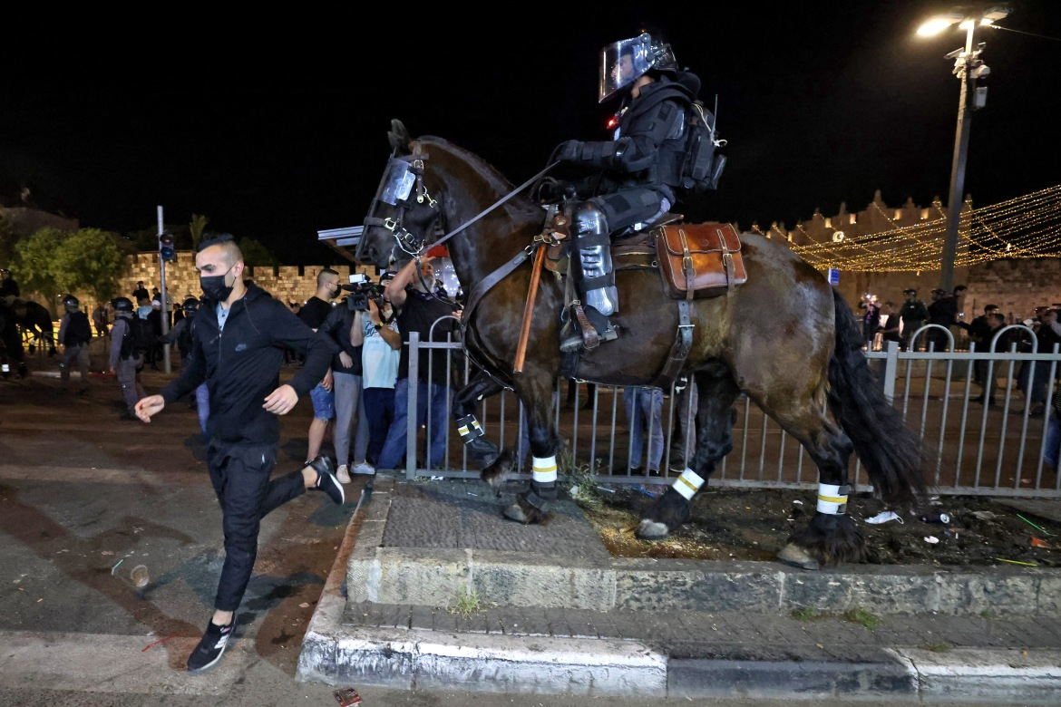 Mounted Israeli security forces chase away Palestinians gathering in Jerusalem's Old City. [Emmanuel Dunand/AFP]