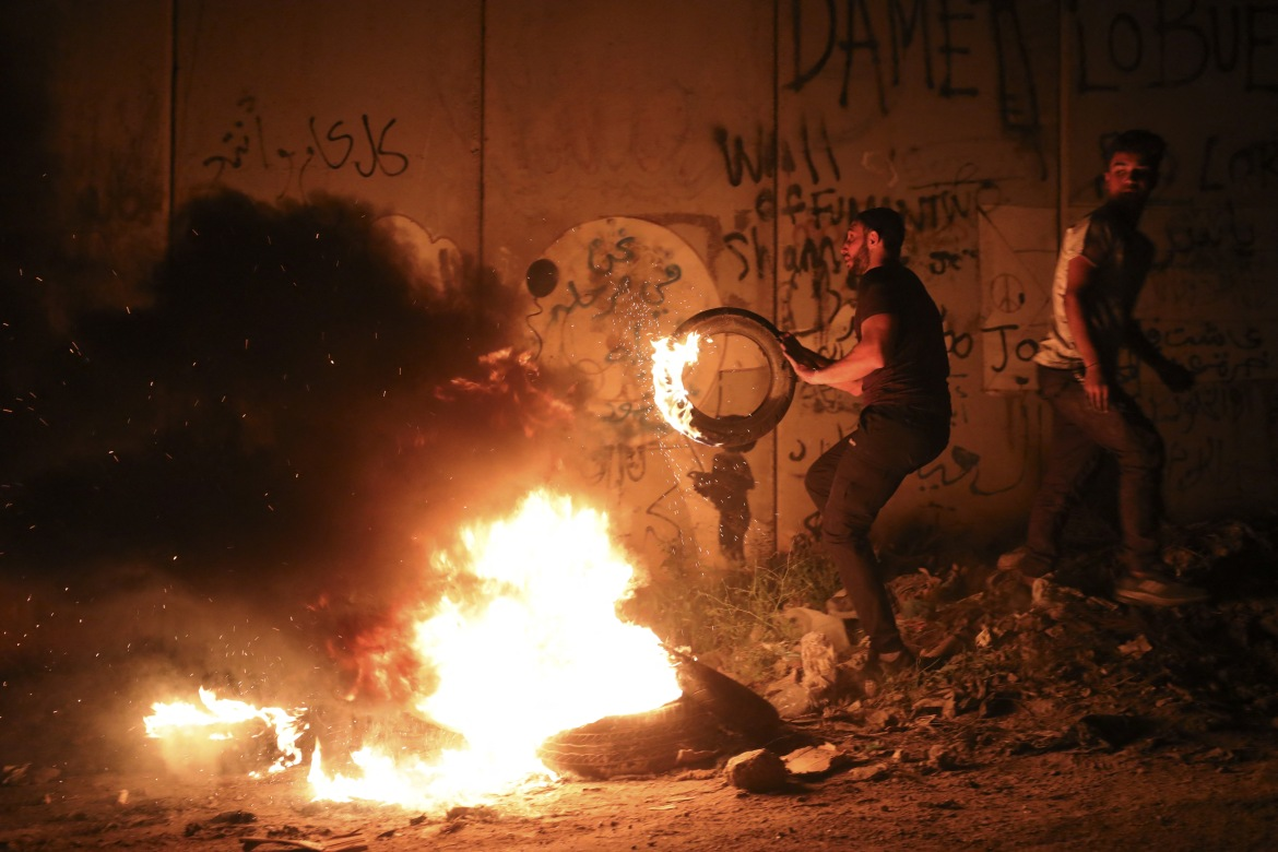 Palestinian demonstrators burn tyres at the Qalandia checkpoint between the West Bank town of Ramallah and Jerusalem, during protests in support of demonstrators in Jerusalem. [Abbas Momani/AFP]