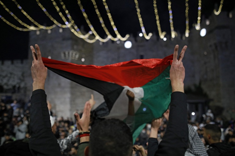 Palestinian protesters wave the national flag outside the Damascus Gate in Jerusalem's Old City on April 26, 2021 [AFP/Ahmad Gharabli]