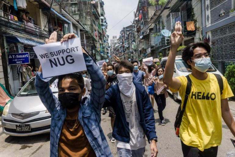 Seorang pengunjuk rasa memegang tanda untuk mendukung Pemerintah Persatuan Nasional sementara yang lain memberi hormat tiga jari selama demonstrasi menentang kudeta militer di Yangon File STR / AFP