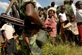 Young villagers watch a Democratic Republic of the Congo commando on October 8, 2005, in Aba, Northern Ituri [File: Lionel Healing/AFP]