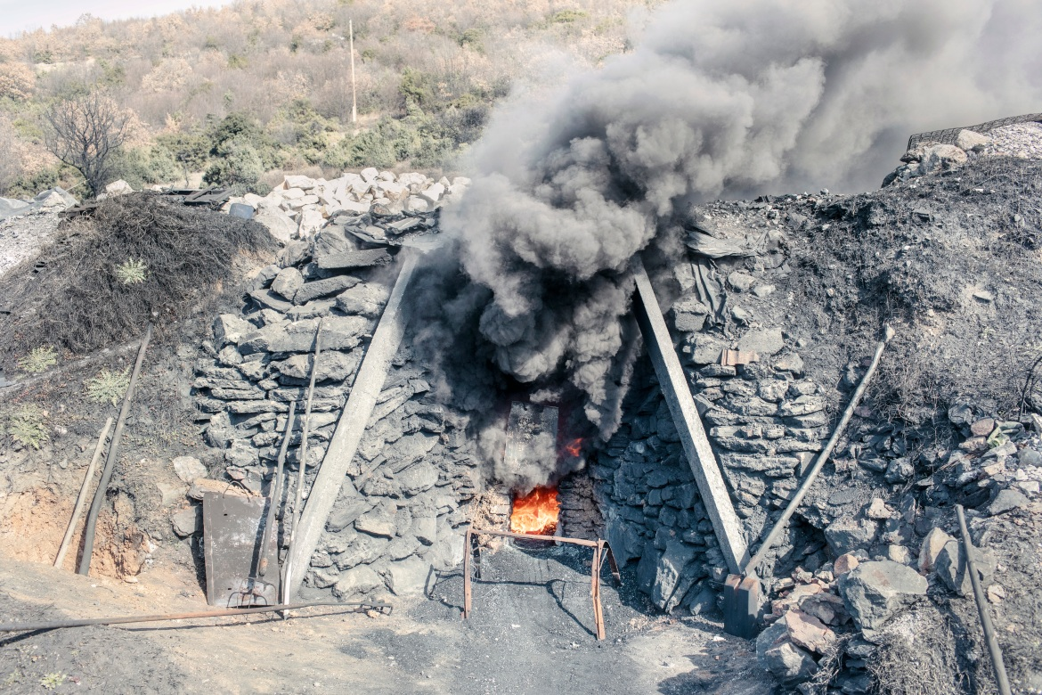 Truck tyres are burned as fuel in an outdoor quicklime kiln in the hills surrounding the village of Kosturino, near the town of Strumica. In Kosturino, there is a tradition handed down from one generation to another to create a long-lasting whitewash. [Stefano Morelli/Al Jazeera]