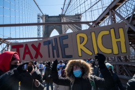 "Protesters hold a ""tax the rich"" sign to demand funding for excluded workers in the New York state budget on March 5, 2021 in New York City. [DAVID DEE DELGADO/GETTY IMAGES VIA AFP] (AFP)"