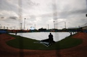 The grounds crew lays the tarp down on the field in anticipation of approaching inclement weather prior to the game between the Toronto Blue Jays and the Los Angeles Angels in Dunedin, Florida on Saturday [Douglas P. DeFelice/Getty Images via AFP]