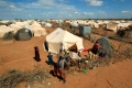 Refugees stand outside their tent at the Ifo Extension refugee camp in Dadaab, near the Kenya-Somalia border in Garissa County, Kenya, in 2011 [File: Thomas Mukoya/Reuters]