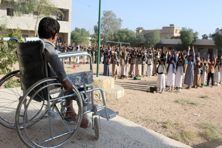 Muhammad al-Shadheli, nine, who survived an August 2018 Saudi-led air strike on a school bus, sits in a wheelchair during the morning drill at his school in Saada province, Yemen on October 6, 2018 [File: Reuters/Naif Rahma]