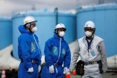 Workers in front of storage tanks for radioactive water at the Fukushima Daiichi nuclear power plant. Japan has confirmed it will release the water into the sea [File: Issei Kato/Reuters]
