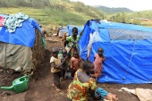 Internally displaced Congolese families near their makeshift shelters at an unofficial camp in Barriere, Ituri province, eastern DRC [File: Olivia Acland/Reuters]