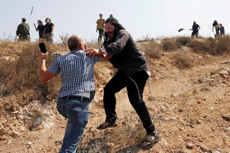A Palestinian demonstrator scuffles with an Israeli settler during a protest against settlements [File: Mohamad Torokman/Reuters]