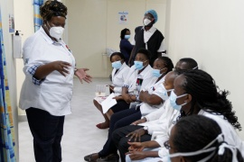 A health worker talks to her colleagues as they prepare to receive the Oxford-AstraZeneca vaccine under the COVAX scheme against COVID-19 at the Kenyatta National Hospital in Nairobi, Kenya on March 5, 2021 [Reuters/Monicah Mwangi]